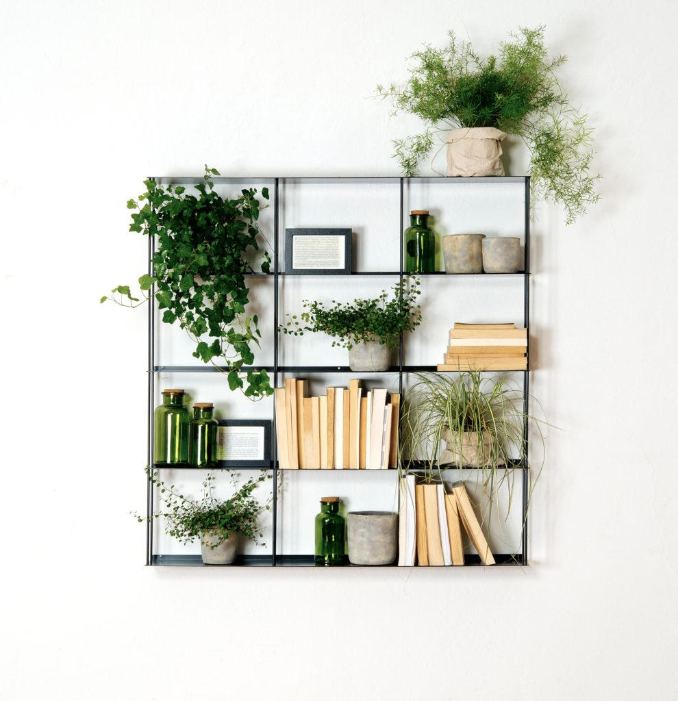 Black metal bookcase with 12 small niches. Some of the niches are filled with plants and decorations, others are filled with books.