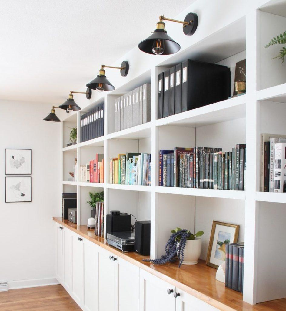 Floor-to-ceiling white wooden bookcase with several niches for books. At the top were placed lamps that facilitate the search for titles.