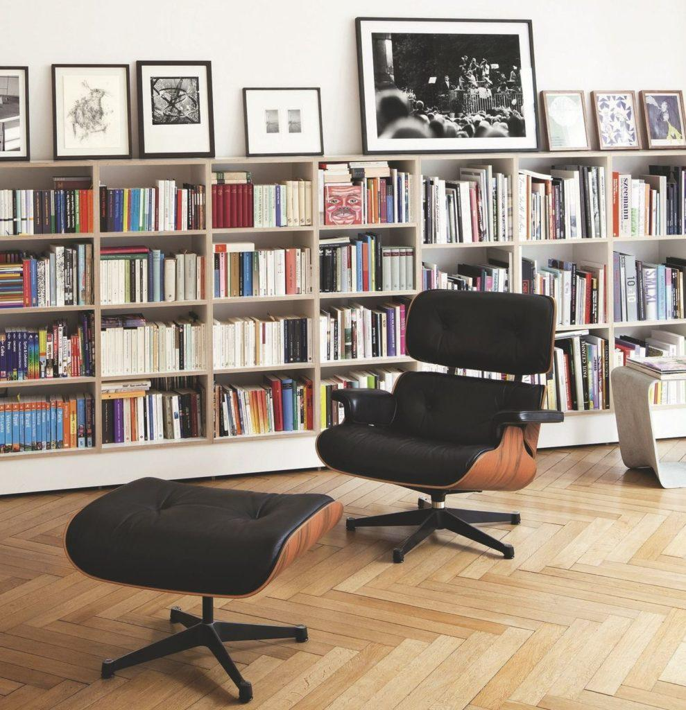 In the foreground is a comfortable black armchair with woody finishes. In the background is a medium height bookcase with books and several paintings.