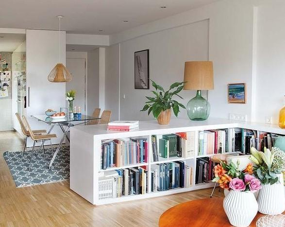 Living and dining room integrated with neutral decor. Among them, there is a piece of furniture less than 1 m high that houses the library.
