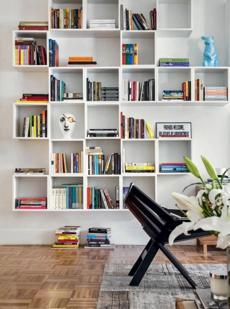 Niches fixed directly to the wall and with small piles of books distributed in each one of them.