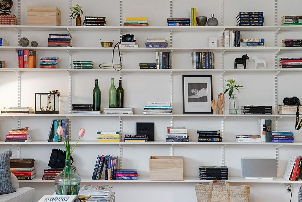 Shelves with stacks of books vertically and horizontally, interspersed with decorative elements such as vases, bottles and sculptures.