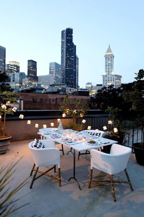 Terrace decorated with lights, tables and armchairs with toothpicks.